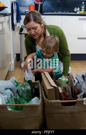 Garçon mise en bouteille de lait en plastique panier de recyclage sur plancher de la cuisine, penché au-dessus de la femme derrière lui Banque D'Images
