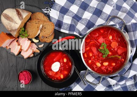 Soupe rouge betterave délicieux avec des haricots blancs, ou bortsch dans une casserole en acier inoxydable et pan en noir bol avec pain de seigle et du bacon tranché fumé sur Banque D'Images