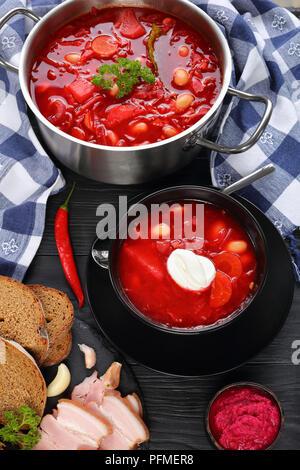 Soupe rouge betterave délicieux avec des haricots blancs, ou bortsch dans une casserole en acier inoxydable et pan en noir bol avec le pain de seigle et de lard fumé sur table, Banque D'Images