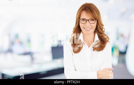 Portrait of a woman financière réussie les bras croisés dans son bureau. Banque D'Images