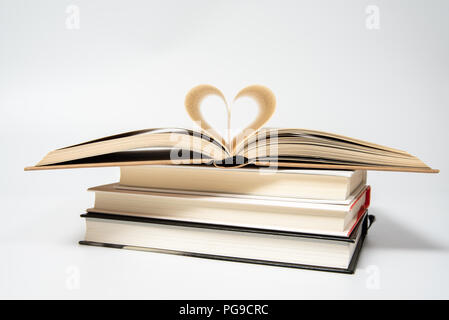 Close up de livre ouvert avec forme du cœur de deux pages, isolé sur fond blanc. Banque D'Images