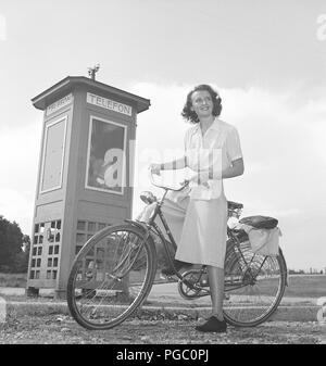 1940 femme sur un vélo. Une jeune femme sur un vélo pour femmes à côté d'une cabine téléphonique. Remarquez les détails de la protection sur la roue arrière pour protéger les vêtements chers d'être pris dans la roue. La Suède des années 40. Kristoffersson Photo M47-1 Banque D'Images