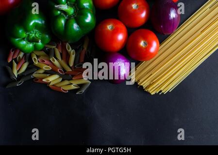 Ingrédients pour les pâtes italiennes. Tomates, poivrons, oignons, pâtes. Mise à plat. Banque D'Images