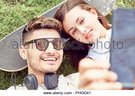 Teenage couple lying on skateboard et selfies Banque D'Images