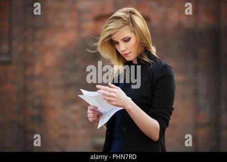 Jeune femme d'affaires la lecture d'une lettre d'impôt on city street Banque D'Images