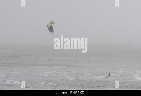 Tirella mention, comté de Down, Irlande du Nord. 02 septembre 2018. Uk - une breezy day avec un vent onshore. Les nuages bas et le brouillard de la mer dire mauvaise visibilité sur la côte est de l'Irlande du Nord. Un kiite-surfer sur les vagues. Crédit: David Hunter/Alamy Live News. Banque D'Images