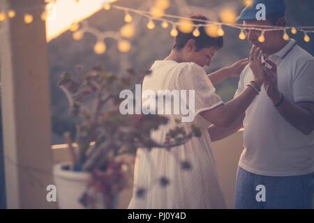 Couple danse romantique avec amour et romance au cours de la vers le bas dans la soirée à la terrasse. Piscine activité de loisirs pour l'âge moyen ne Banque D'Images