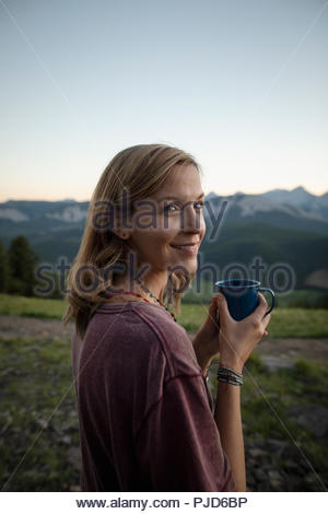 Portrait souriant, carefree woman drinking coffee in field, Alberta, Canada Banque D'Images