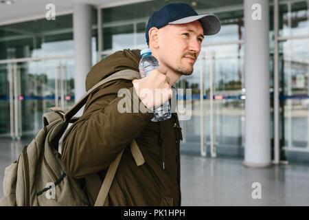 Un voyageur met sur un sac à dos ou la soulève et tient une bouteille d'eau dans sa main. Une personne va sur un autre voyage ou va prendre un repos. Banque D'Images