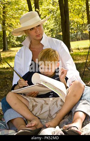 Artiste féminin passé du temps au parc public et l'utilisation des scènes de peinture son fils dans certains. Jour de joie pour elle et son fils. Banque D'Images