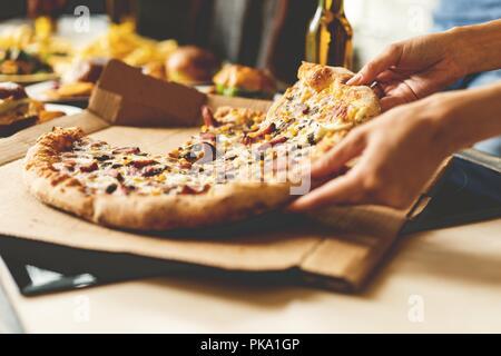 Les amis de prendre des tranches de pizza savoureuse de la plaque, vue en gros plan. Banque D'Images