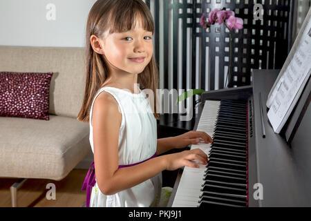 Fillette de six ans a jouer du piano Banque D'Images