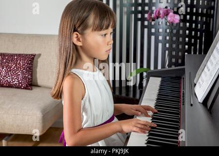 Fillette de six ans pratiquant le piano Banque D'Images