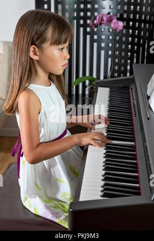 Fillette de six ans a pratiquer son piano Banque D'Images