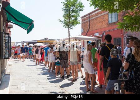 Les touristes la mise en queue sur l'île de Murano, Venise, Vénétie, Italie dans la Calle Bresaggio pour prendre le vaporetto à Burano. Longue file de gens, attente, foule, Banque D'Images