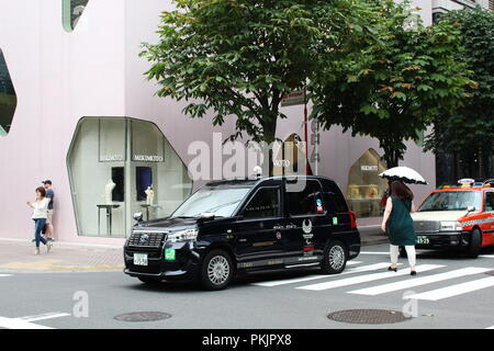 Une Toyota JPN Taxi avec les Jeux Olympiques de Tokyo 2020 logo sur va-t-il sur un passage pour piétons en face de la Toyo Ito-conçu Mikimoto Ginza 2 store à Tokyo. Banque D'Images