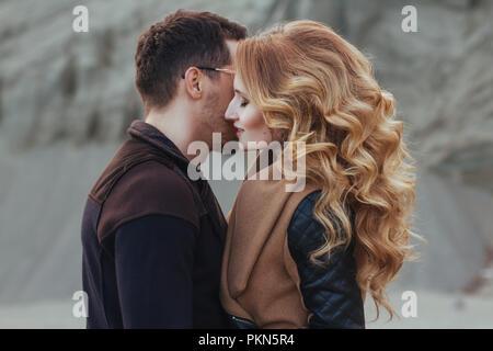 Beau couple amoureux à la Saint-Valentin. Happy young couple en train de marcher sur la plage de sable de montagne sur un jour nuageux Banque D'Images