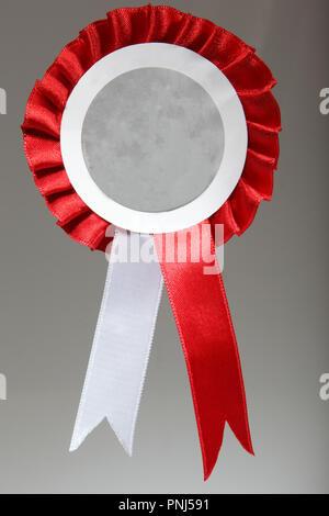 Badge de rubans rouge et blanc sur fond gris avec texte ou photo salon Banque D'Images