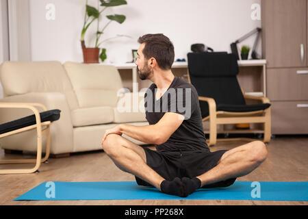 Homme tiwst postures de yoga tout en étant à la maison. Formation à la mobilité. Banque D'Images