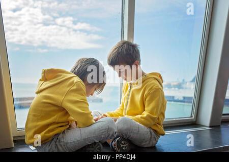 Beaux enfants, à bord du ferry, qui voyagent pour des vacances d'été Banque D'Images