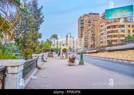 Le CAIRE, ÉGYPTE - Le 23 décembre 2017: Le vieil homme repose sur le banc en corniche El-Nil street et profiter de la vue sur les jardins, qui mène le long de la N Banque D'Images