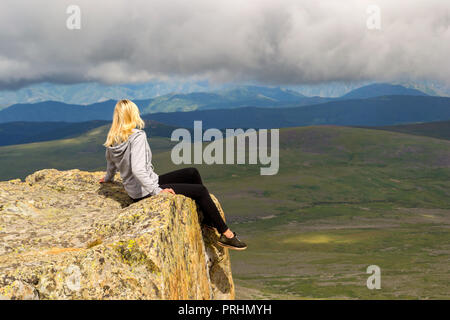 La fille blonde se trouve dangereusement seul sur le bord de la falaise au-dessus de l'abîme dans les montagnes de l'Altaï, accrochant ses jambes vers le bas sur le lac et loo Banque D'Images