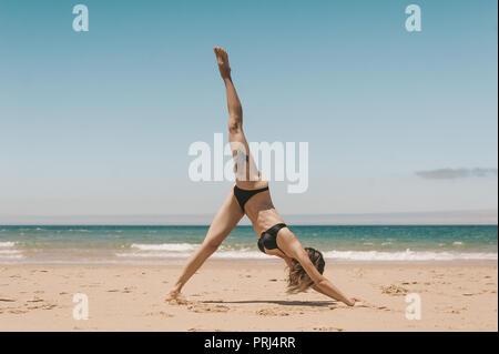 Vue latérale du woman practicing yoga pose chien tête en bas sur la plage de sable Banque D'Images