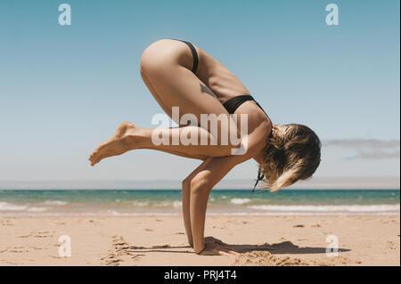 Side view of young woman in bikini noir pratiquant Bakasana yoga position on sandy beach Banque D'Images