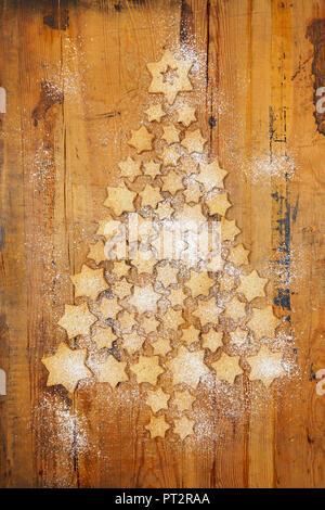 Des biscuits en forme d'étoiles formant Arbre de Noël sur fond de bois Banque D'Images