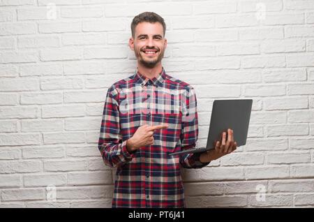 Jeune adulte homme sur mur de briques à l'aide de pointage pour ordinateur portable très heureux avec la main et des doigts Banque D'Images