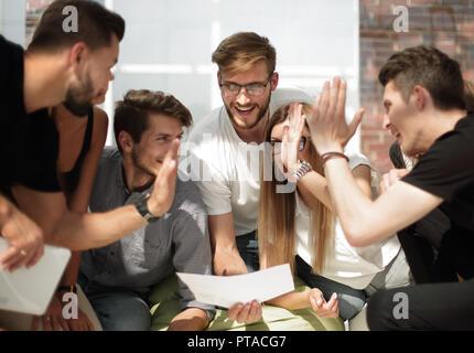Les jeunes entrepreneurs donnant à chaque autre un cinq lors d'une réunion informelle Banque D'Images