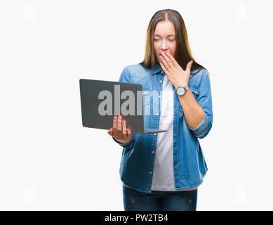 Young caucasian woman using laptop sur fond isolé couvrir la bouche à part choqué avec honte pour erreur, expression de la peur, peur en silenc Banque D'Images