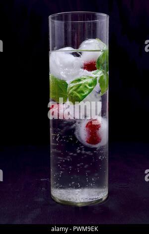 Des cubes de glace avec des framboises et de basilic dans un verre d'eau Banque D'Images