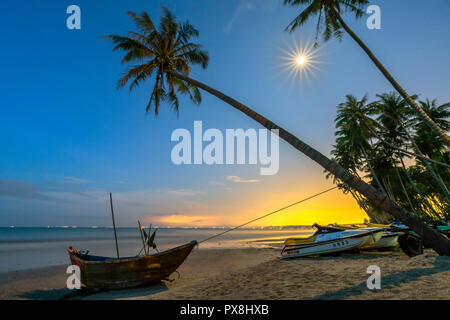 Un brillant clair de lune, sur la belle plage avec cocotiers et incliné vers le bateau du pêcheur au Vietnam village de pêcheurs Banque D'Images