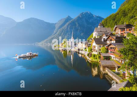 Vue de carte postale classique de la célèbre ville au bord du lac de Hallstatt avec navire traditionnel dans la belle lumière du matin au lever du soleil en été, Salzkammergut, Autriche Banque D'Images