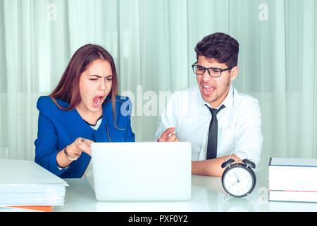 A souligné en colère contre la femme et l'homme d'affaires avec ordinateur portable à le regarder assis à table de crier sur ordinateur. Les émotions négatives dans la vie de bureau. Problèmes à Banque D'Images