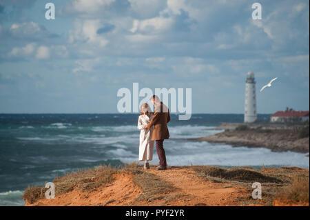 Couple à la mode dans les manteaux homme et femme sur la côte de la mer orageuse avec balise blanche Banque D'Images