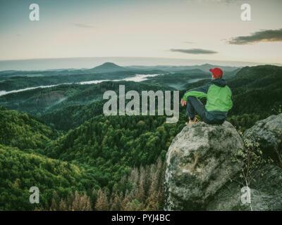 Hiker homme prendre un repos sur le pic. Veste Coupe-vent vert avec Voyageur repose au sol et admire les sommets Banque D'Images