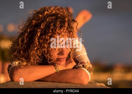 Belle ambiance perdue dans ses pensées et profiter du soleil sur son visage pendant un été, l'heure du coucher du soleil chaud. cheveux blonds moyen age femme. cau Banque D'Images