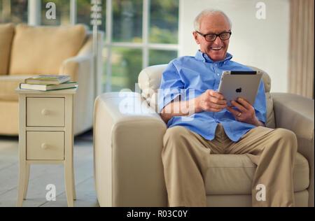 Happy senior man s'amusant à l'aide d'une tablette numérique. Banque D'Images