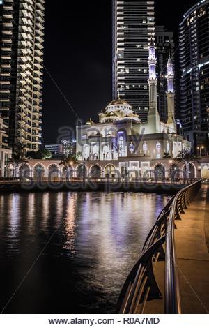 Mosquée de nuit à Dubaï, aux Emirats Arabes Unis à Dubai Marina. Reflet des lumières de la mosquée dans la baie de l'eau. Banque D'Images