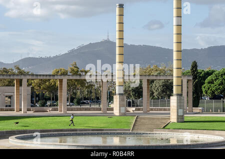 Homme marchant dans l'herbe avec chien sur Plaça d'Europa dans Anella Olímpica de Montjuic Barcelone, Espagne. Banque D'Images