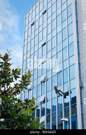 Nettoyant à travailler sur une façade de verre suspendue Banque D'Images