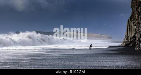Islande étonnante en hiver - des paysages à couper le souffle et des paysages gelés - homme qui court sur la plage volcanique sous l'écrasement des vagues - image puissante Banque D'Images