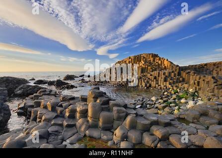 L'Irlande du Nord, le comté d'Antrim, la Chaussée des Géants, motif nuage spectaculaire sur les roches au coucher du soleil. Banque D'Images