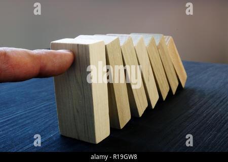 Concept de gestion des risques de l'entreprise. Hand holding blocks de tomber. Effet domino. Banque D'Images