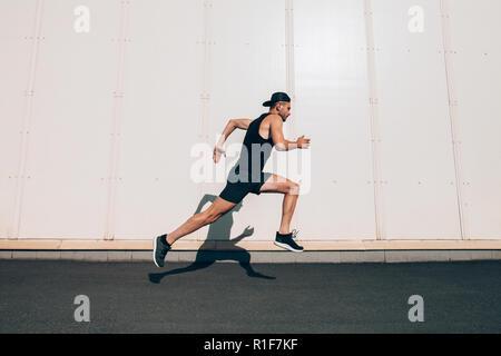 Runner homme courir vite en ville industrielle. Le sport, l'athlétisme, fitness, jogging activité Banque D'Images
