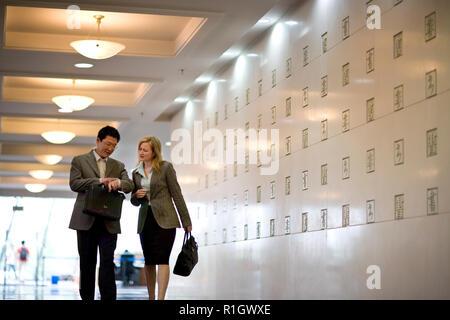 Mid-adult woman marchant dans un couloir avec une collègue mâles adultes. Banque D'Images