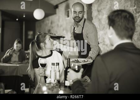 Poli garçon portant des plats commandés aux jeunes smiling couple at restaurant Banque D'Images