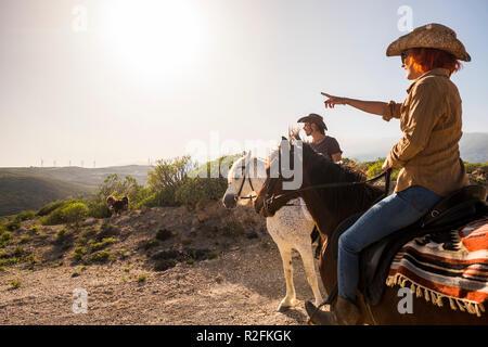 Couple en vacances à Tenerife monter à cheval dans la nature. moulin à vent sur l'arrière-plan et couleur ensoleillée journée. chien et animaux activité de loisirs de plein air pour un traitement efficace et de l'amitié Banque D'Images